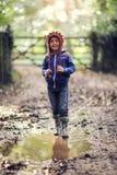 Enfant marchant dans la boue Photos libres de droits