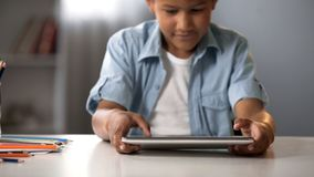 Enfant masculin jouant avec enthousiasme sur le comprimé, dépendance de jeu, problème de comportement photographie stock libre de droits