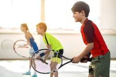 Enfant masculin joyeux jouant le tennis avec des amis Images stock
