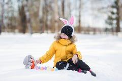 Enfant mettant les oeufs en pastel colorés dans un panier La petite fille mignonne avec un lapin a Pâques au fond blanc de neige Image stock