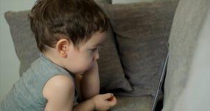 Enfant mignon amusant avec la Tablette Little Boy passant le temps libre jouant le jeu mobile dans et écrase le lumineux clips vidéos