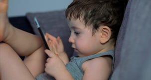 Enfant mignon amusant avec la Tablette Little Boy passant le temps libre jouant le jeu mobile dans et écrase le lumineux banque de vidéos