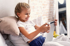 Enfant mignon appréciant l'instrument numérique Photographie stock libre de droits