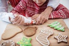Enfant mignon appréciant le processus de décorer la pâtisserie de vacances Image libre de droits