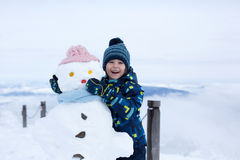 Enfant mignon, bonhomme de neige de construction et jouer avec lui sur le bâti Photos stock