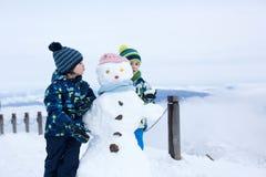 Enfant mignon, bonhomme de neige de construction et jouer avec lui sur le bâti Photographie stock libre de droits