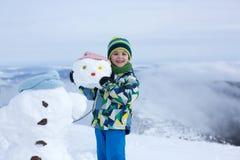 Enfant mignon, bonhomme de neige de construction et jouer avec lui sur le bâti Photos libres de droits