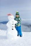 Enfant mignon, bonhomme de neige de construction et jouer avec lui sur le bâti Images libres de droits