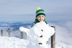 Enfant mignon, bonhomme de neige de construction et jouer avec lui sur le bâti Photo libre de droits