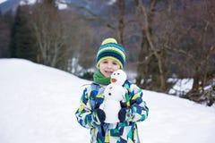 Enfant mignon, bonhomme de neige de construction et jouer avec lui sur le bâti Image libre de droits