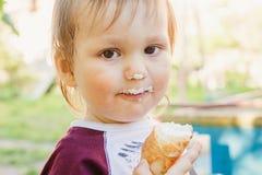 Enfant an mignon dégoûtant avec le gâteau pendant l'été dehors Photo stock
