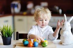 Enfant mignon d'enfant en bas âge jouant avec des oeufs de pâques le jour de Pâques Image libre de droits