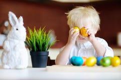 Enfant mignon d'enfant en bas âge jouant avec des oeufs de pâques le jour de Pâques Images libres de droits