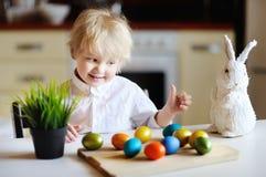 Enfant mignon d'enfant en bas âge jouant avec des oeufs de pâques le jour de Pâques Images stock