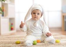 Enfant mignon de bébé dans le sittng de costume de lapin sur le froor dans la crèche photographie stock libre de droits
