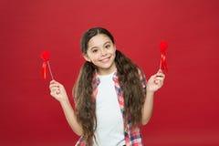 Enfant mignon de fille avec des coeurs Fille d'enfant avec le fond rouge de longs cheveux Célébrez le jour de valentines Vacances image libre de droits