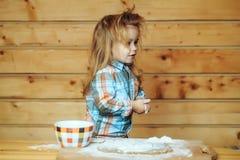 Enfant mignon faisant cuire avec la pâte, la farine et la cuvette sur le bois Photo libre de droits