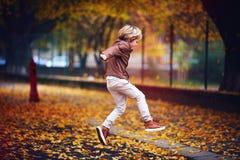Enfant mignon, garçon dans la veste en cuir ayant l'amusement à la rue d'automne, sautant et fonctionnant autour sur le tapis des Image stock