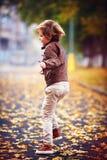 Enfant mignon, garçon dans la veste en cuir ayant l'amusement à la rue d'automne, sautant et fonctionnant autour sur le tapis des Image libre de droits