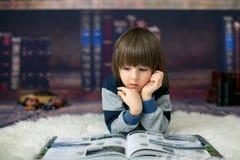 Enfant mignon, garçon, lisant un livre à la maison devant la bibliothèque Image libre de droits