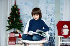 Enfant mignon, garçon, lisant un livre, se reposant sur une chaise Images stock