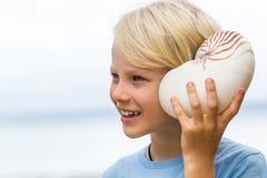 Enfant mignon heureux écoutant la mer dans la coquille de nautilus Photo libre de droits