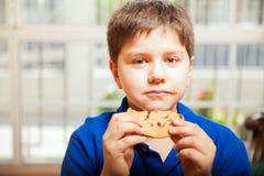 Enfant mignon mangeant un grand biscuit Images libres de droits