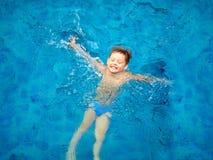 Enfant mignon, natation de garçon dans l'eau de piscine, vue supérieure Photos stock
