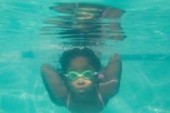 Enfant mignon posant sous l'eau dans la piscine Photos stock