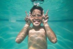 Enfant mignon posant sous l'eau dans la piscine Images libres de droits