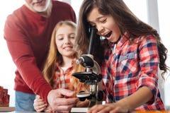 Enfant mignon stupéfait observant les particules microscopiques Photographie stock libre de droits