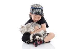 Enfant musulman mignon jouant avec le chat tigré Photos stock