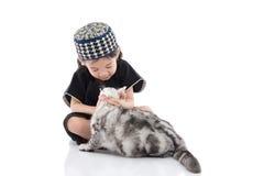 Enfant musulman mignon jouant avec le chat tigré Image libre de droits
