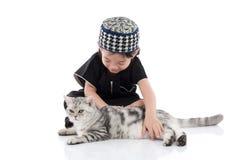 Enfant musulman mignon jouant avec le chat tigré Photo libre de droits