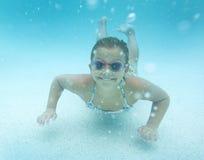Enfant nageant sous l'eau dans une piscine extérieure images stock