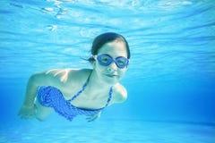 Enfant nageant sous l'eau dans une piscine extérieure image stock