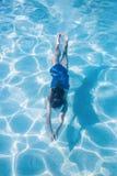 Enfant nageant sous l'eau dans une piscine extérieure photos libres de droits