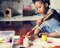 Enfant noir appréciant la peinture de couleur images stock