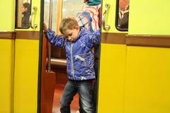 Enfant non identifié essayant de fermer les portes d'une voiture de souterrain Photos libres de droits