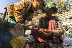 Enfant non identifié et ses parents pendant le déjeuner dans la coupure entre travailler à la décharge Photo libre de droits