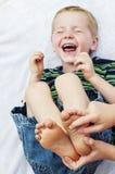 Enfant obtenant aux pieds nus de smiley chatouillé Images libres de droits
