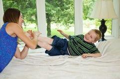 Enfant obtenant le pied chatouillé Photos libres de droits