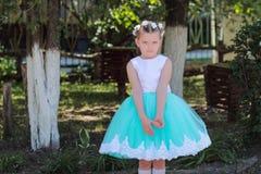 Enfant offensé, petite fille mignonne dans une robe bleue et blanche, enfant avec une guirlande des fleurs artificielles sur sa t Images stock