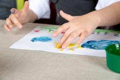 Enfant paiting la peinture avec vos doigts Images stock