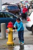 Enfant par un coq du feu Images stock