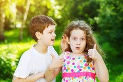 Enfant parlant avec des chuchotements Fille avec des pouces vers le haut Image libre de droits