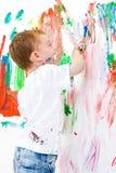 Enfant peignant et ayant beaucoup d'amusement Image libre de droits