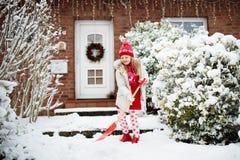 Enfant pellant la neige Petite fille avec l'allée de clairière de pelle après tempête de neige d'hiver  photographie stock