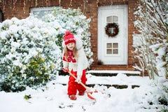 Enfant pellant la neige Petite fille avec l'allée de clairière de pelle après tempête de neige d'hiver  photos stock