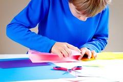 Enfant pliant le papier coloré et faisant l'origami photographie stock libre de droits